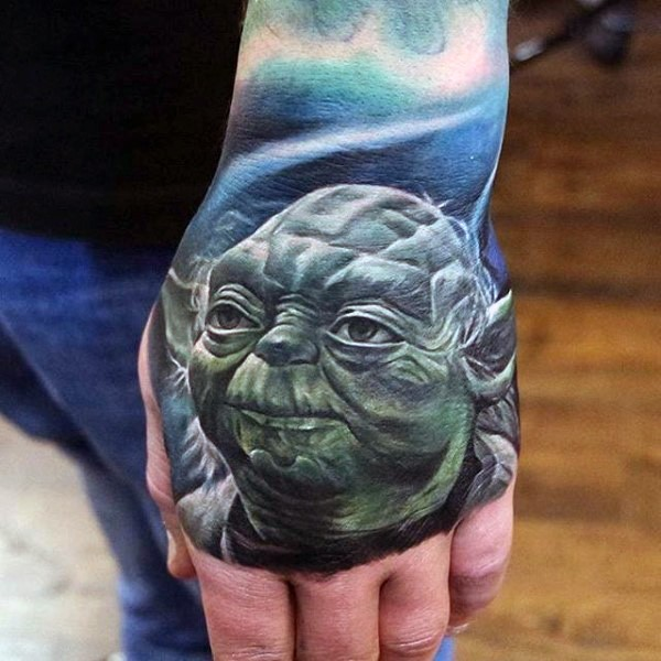 Natural looking detailed colored Yoda portrait tattoo on hand