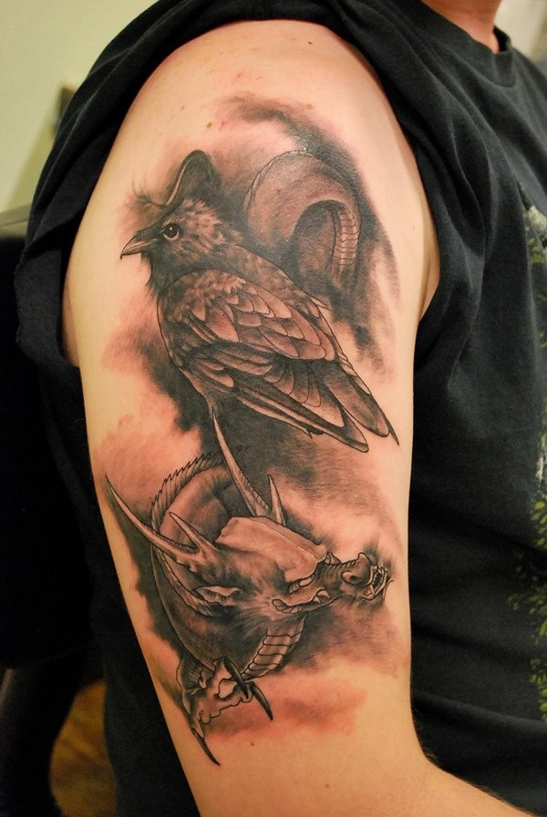 Natural looking detailed crow tattoo on shoulder combined with fantasy dragon