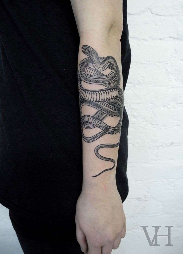 Natural looking little black and white detailed snake tattoo on arm