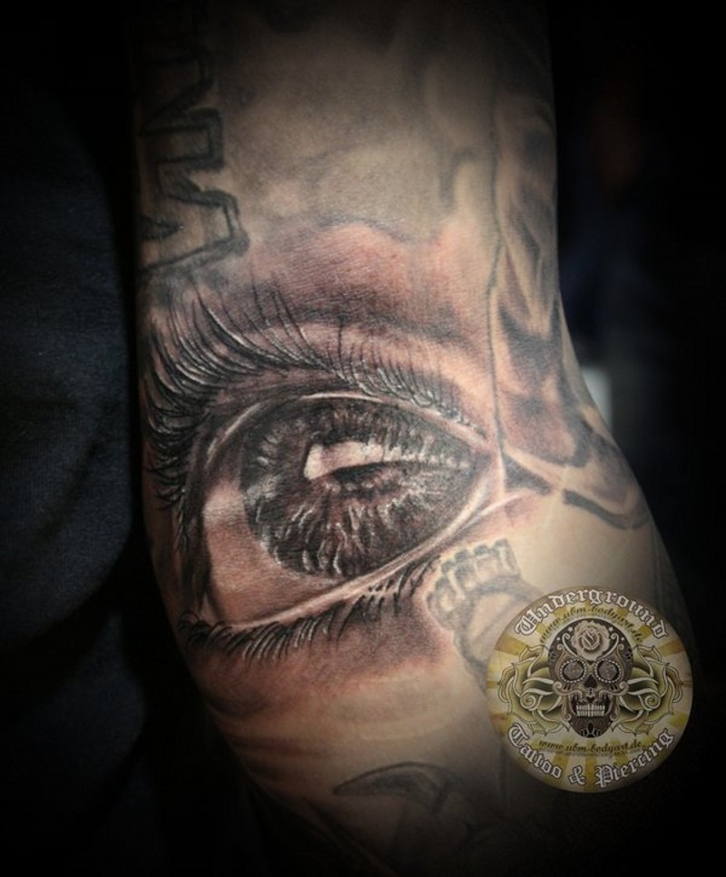 Natural looking little black and white sad eye tattoo on leg
