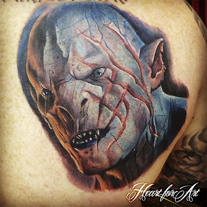 Natural looking very detailed upper back tattoo of The Hobbit orc chief