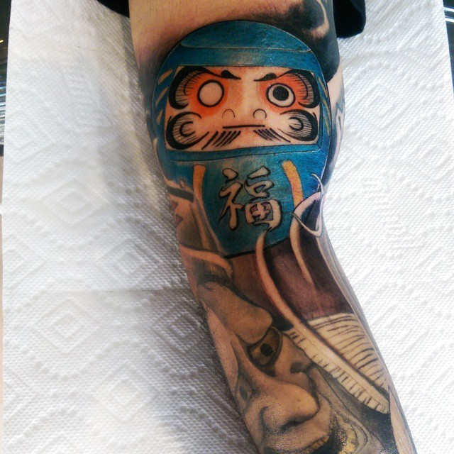 Neo japanese style colored biceps tattoo of daruma doll with demonic mask