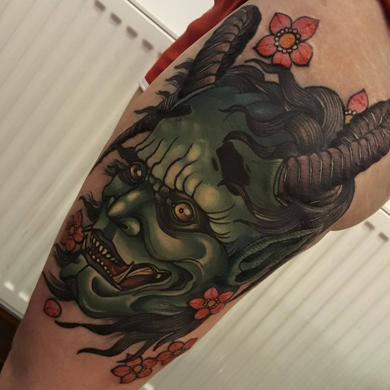 Neo japanese style colored thigh tattoo of demonic face with flowers
