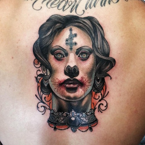 Neo traditional colored back tattoo of zombie woman with cross