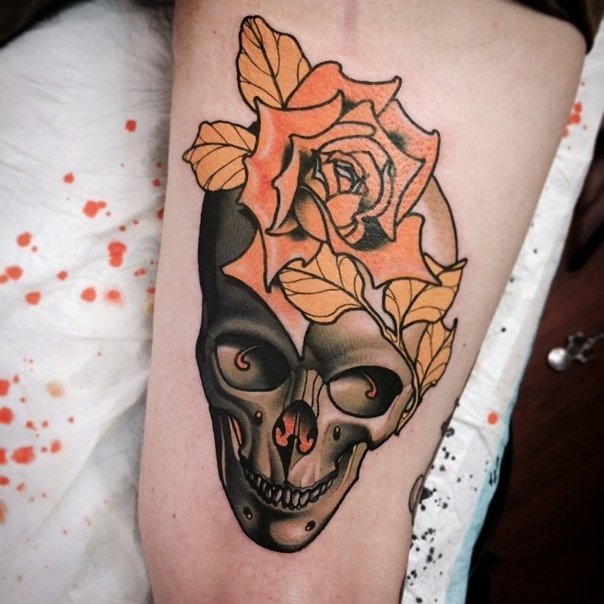 Neo traditional colored thigh tattoo of human skull with big flower