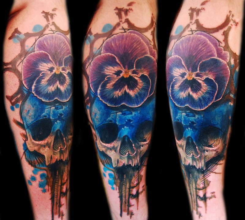 neo traditional style colored arm tattoo of human skull with big flower