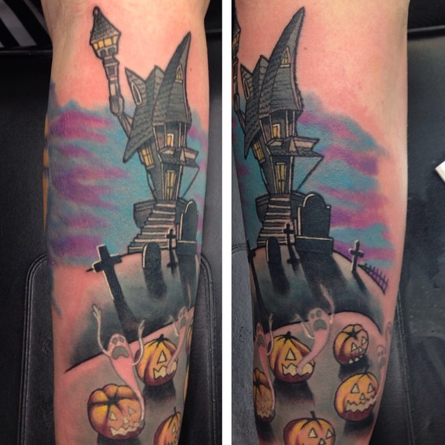 Neo traditional style colored creepy house with cemetery and pumpkins tattoo on arm