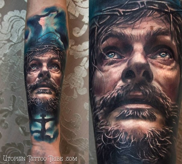 Neo traditional style colored forearm tattoo of Jesus face with cross