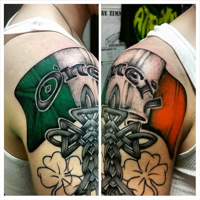 Neo traditional style colored shoulder tattoo of Irish flag with cross and clover