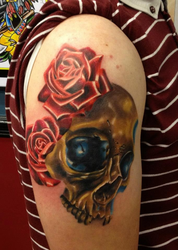Neo traditional style colored shoulder tattoo of golden skull with red roses