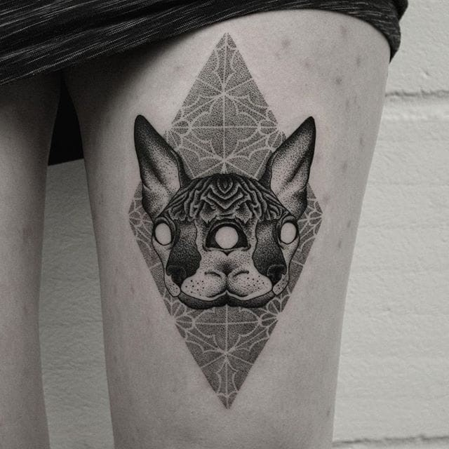 New school black ink dot style thigh tattoo of cat mask with floral ornaments