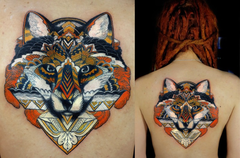 New school illustrative style back tattoo of wolf hear stylized with ornaments