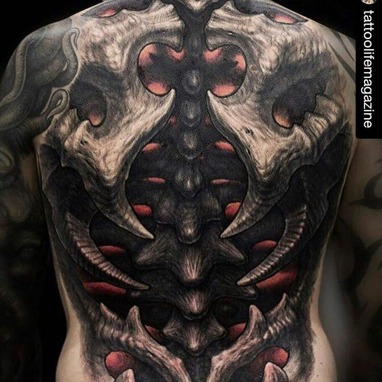 New school style awesome looking whole back tattoo of alien skeleton