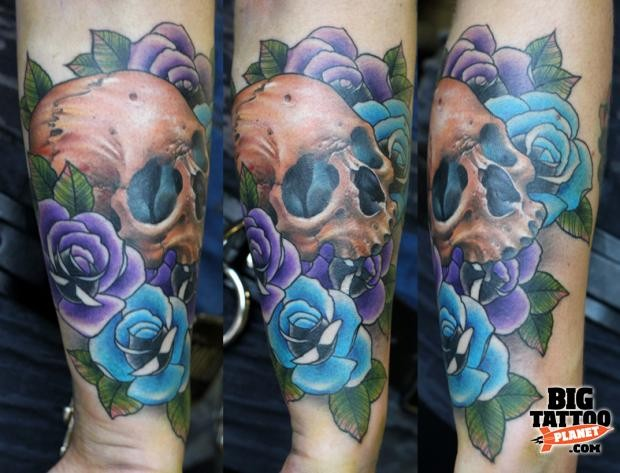 New school style colored forearm tattoo of human skull with various colored roses