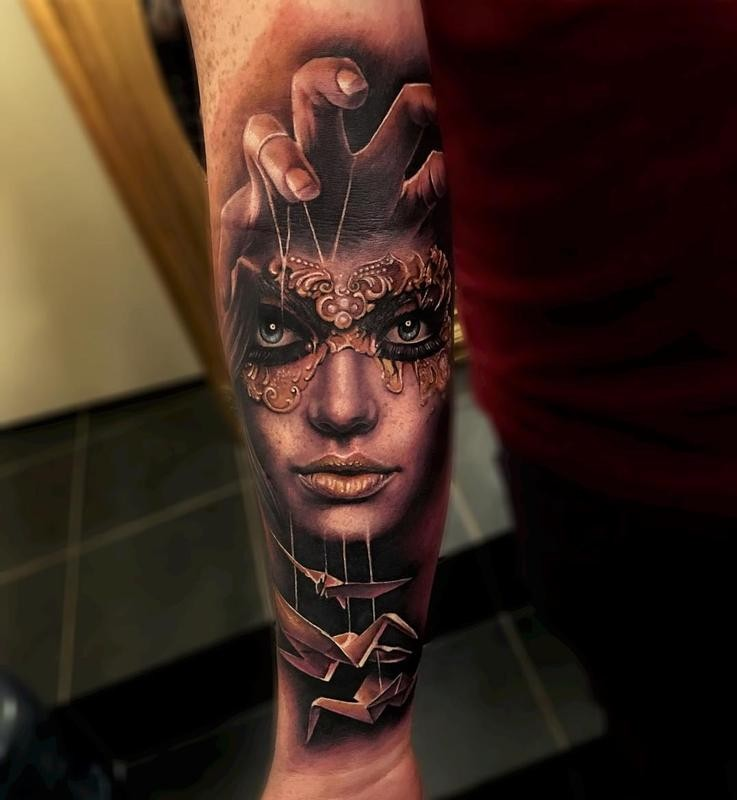 New school style colored forearm tattoo of woman with mask and paper birds