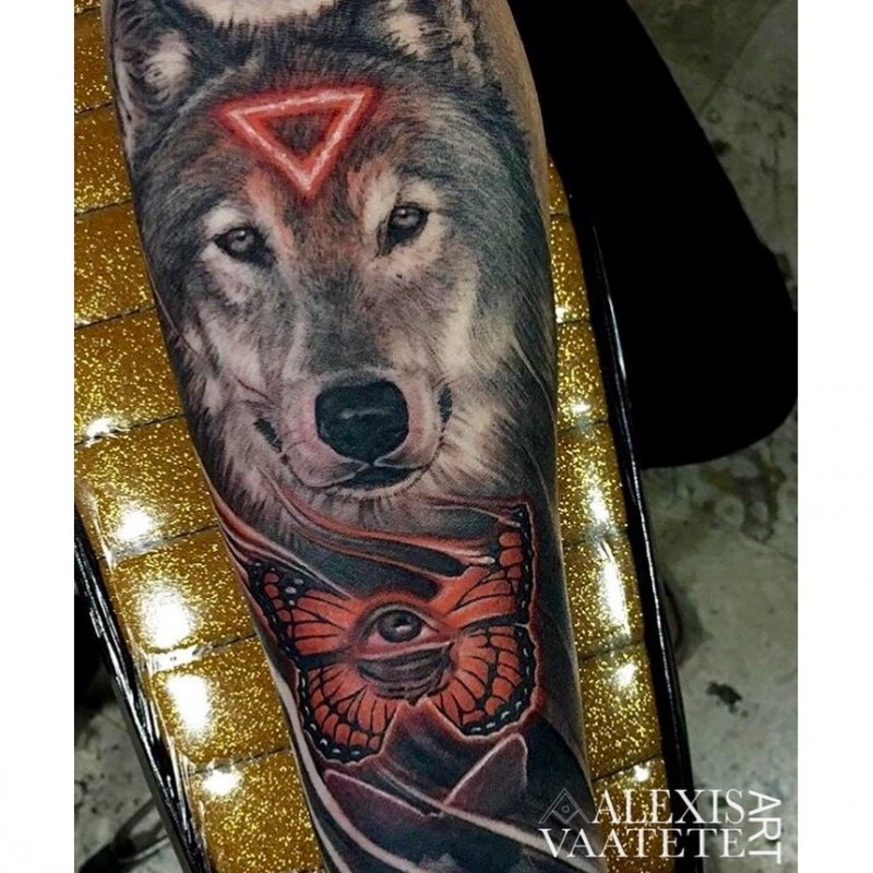 New school style colored forearm tattoo of mystical wolf with red triangle and butterfly