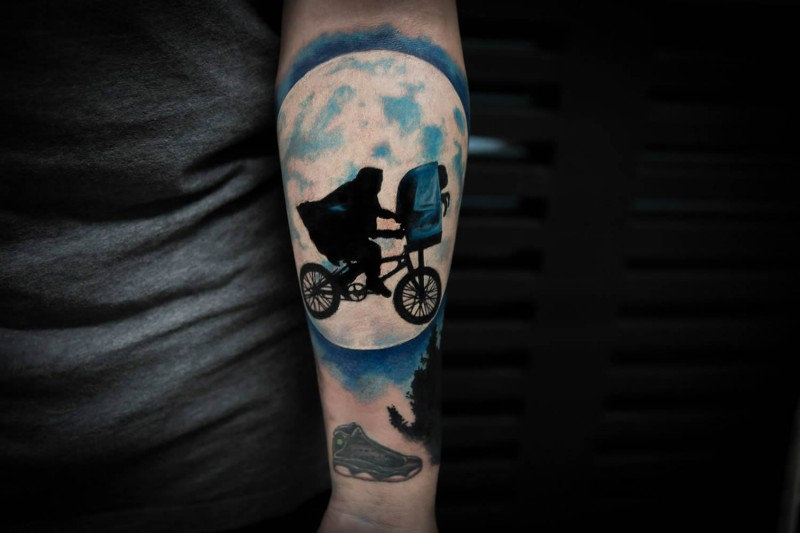 New school style colored forearm tattoo of man with flying bicycle