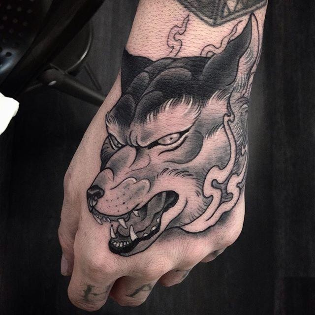 New school style colored hand tattoo of demonic wolf head with flames