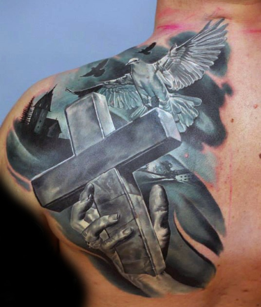 New school style dark colored back and shoulder tattoo of big cross with human hand and flying pigeon