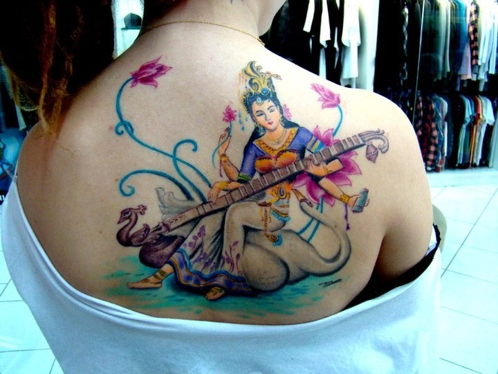 Nice and beautiful looking colored upper back tattoo of Hinduism woman with music instrument