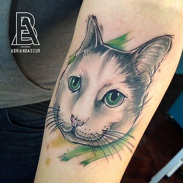 Nice cat with green eyes tattoo on forearm with green haze