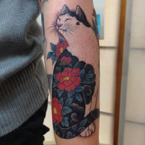 Nice cat with unusual color of red flowers forearm tattoo