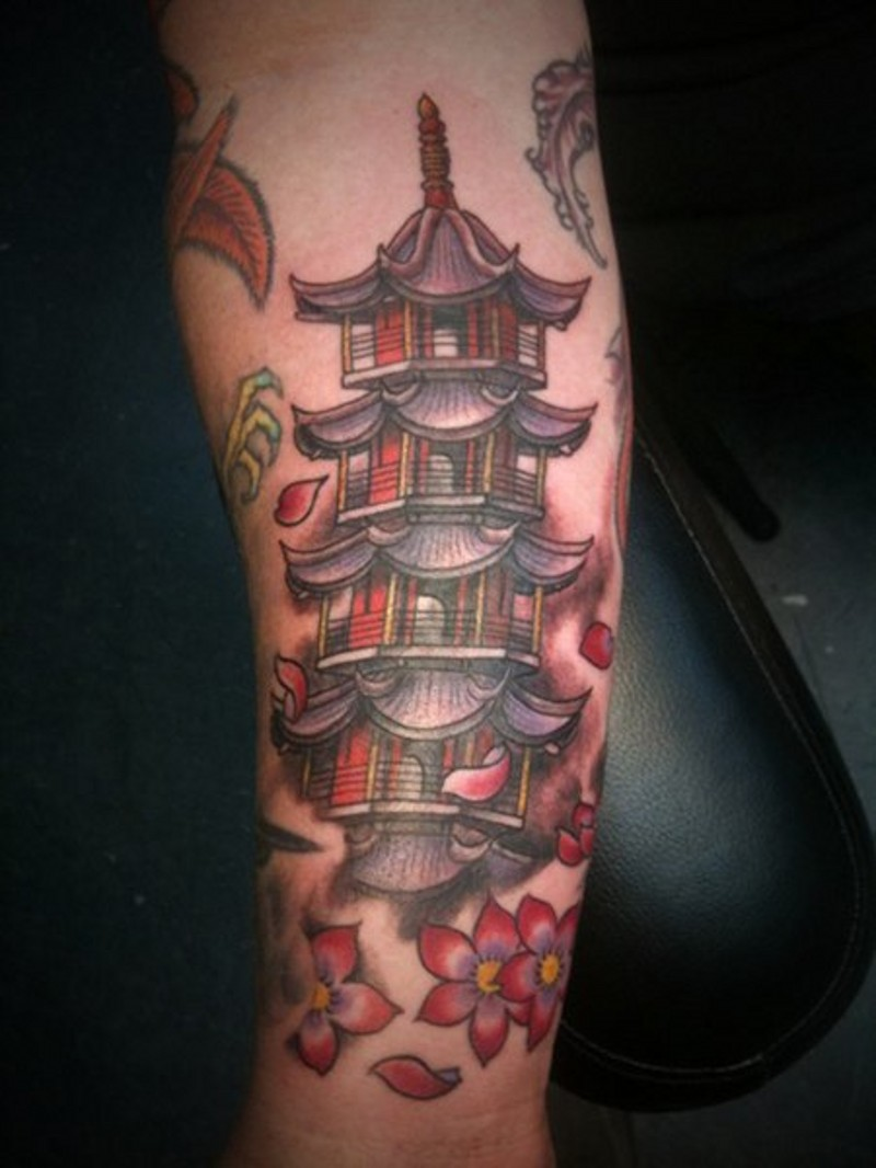 Nice colored forearm tattoo of Asian temple with flowers