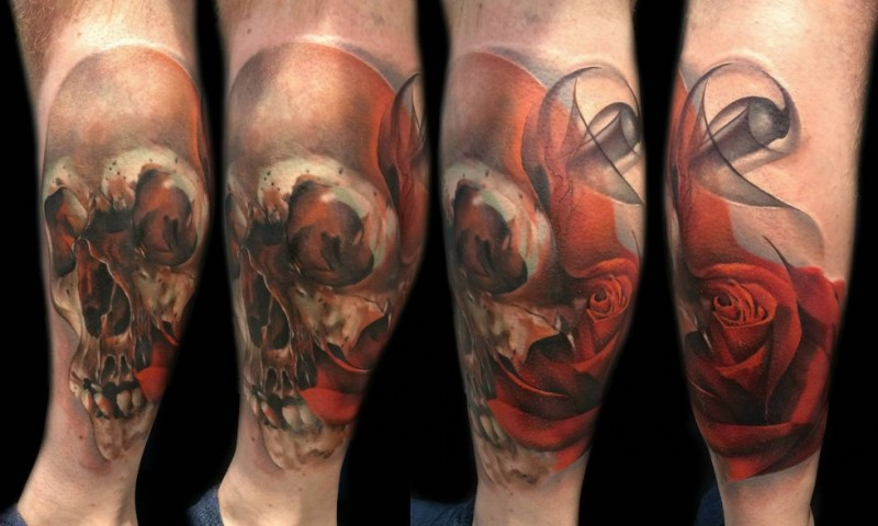Nice designed colorful human skull with rose tattoo on leg