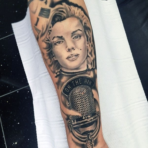 Nice designed Merlin Monroe portrait with microphone tattoo on arm