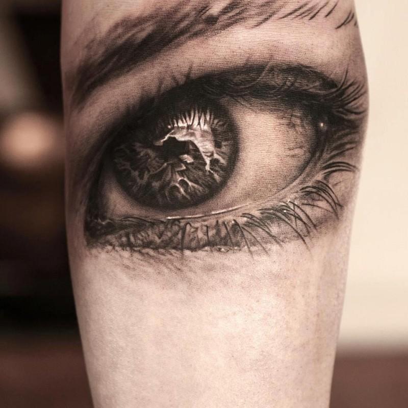 Tatuaggio realistico sul braccio l&quotocchio