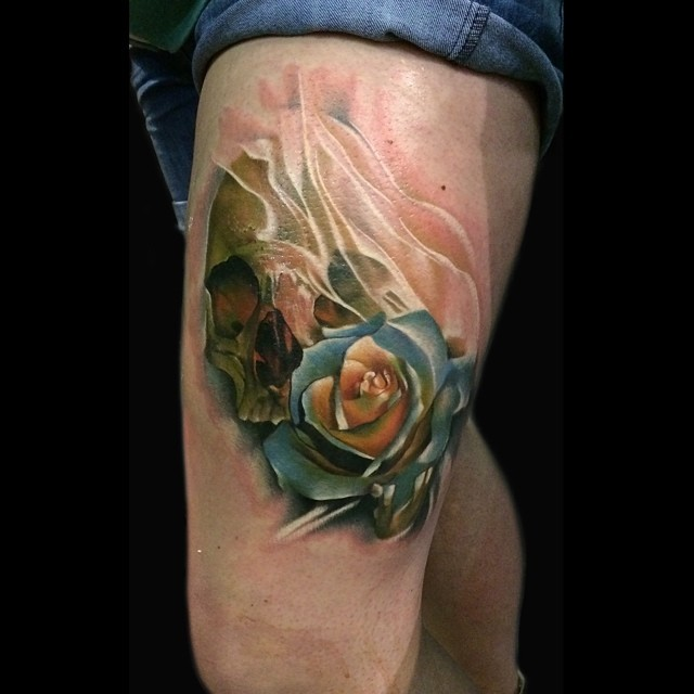 Nice looking 3D colored rose flower tattoo on thigh with human skull