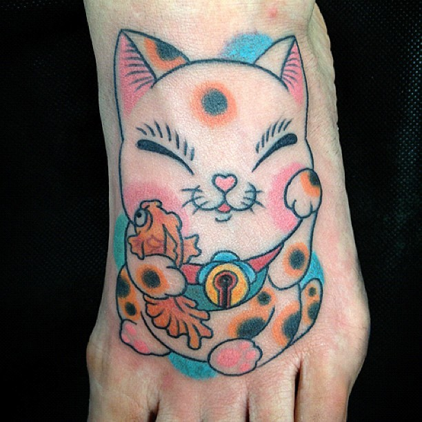 Nice looking cartoon like foot tattoo of smiling maneki neko japanese lucky cat with carp fish