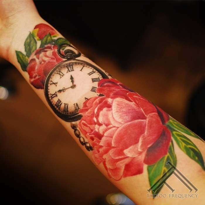 Nice looking colored forearm tattoo of big flower with clock