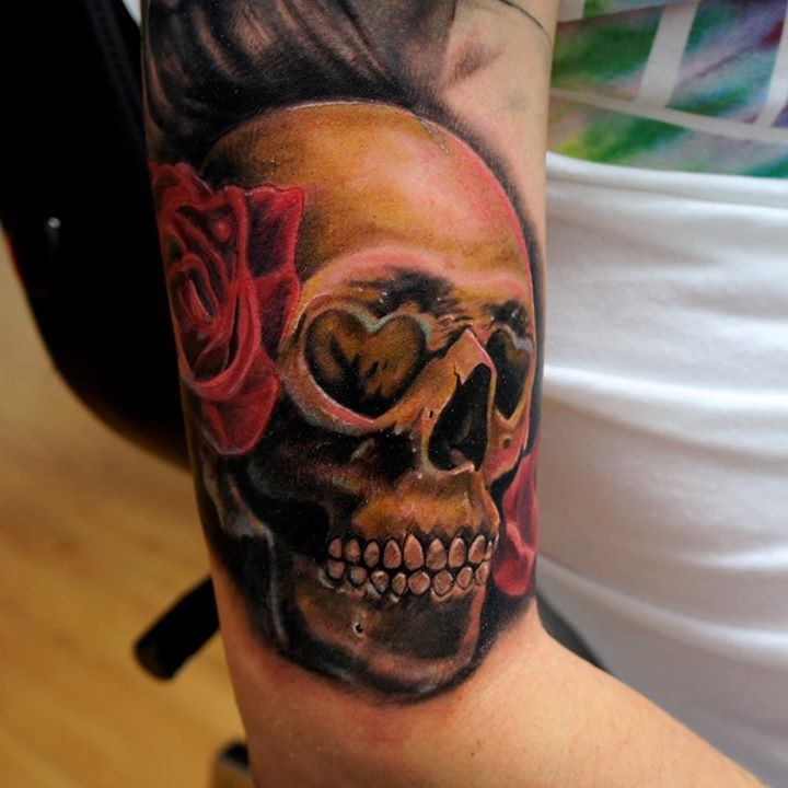 Nice looking colored human skull tattoo on arm with rose