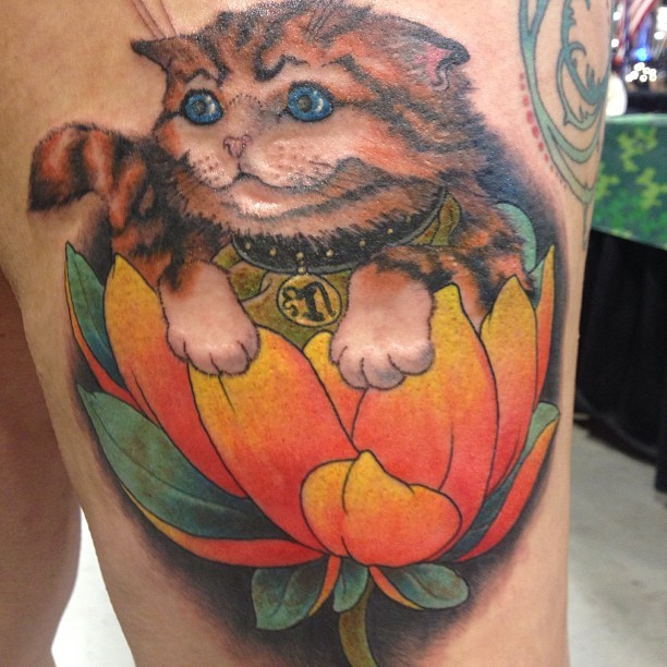 Nice looking homemade style thigh tattoo of maneki neko japanese lucky cat with small flower