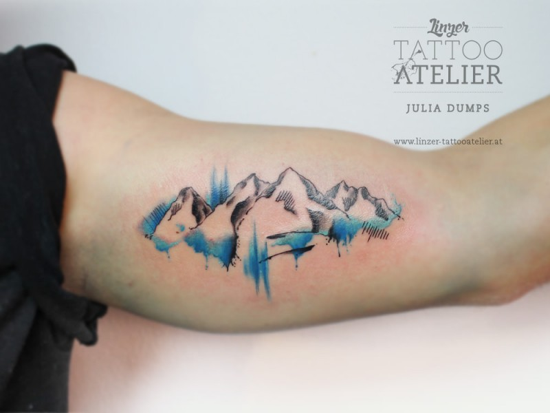 Nice mountain scenery tattoo on biceps by Julia Dumps with watercolor details