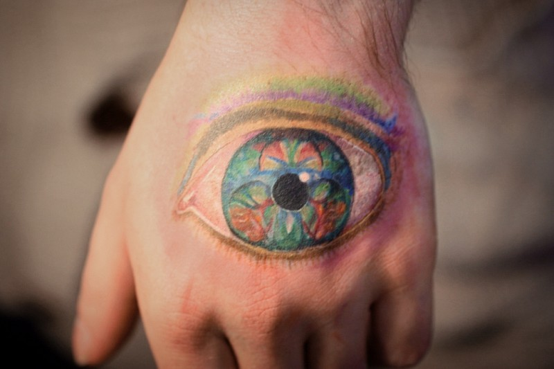 Nice multicolored detailed on hand tattoo of mystical eye