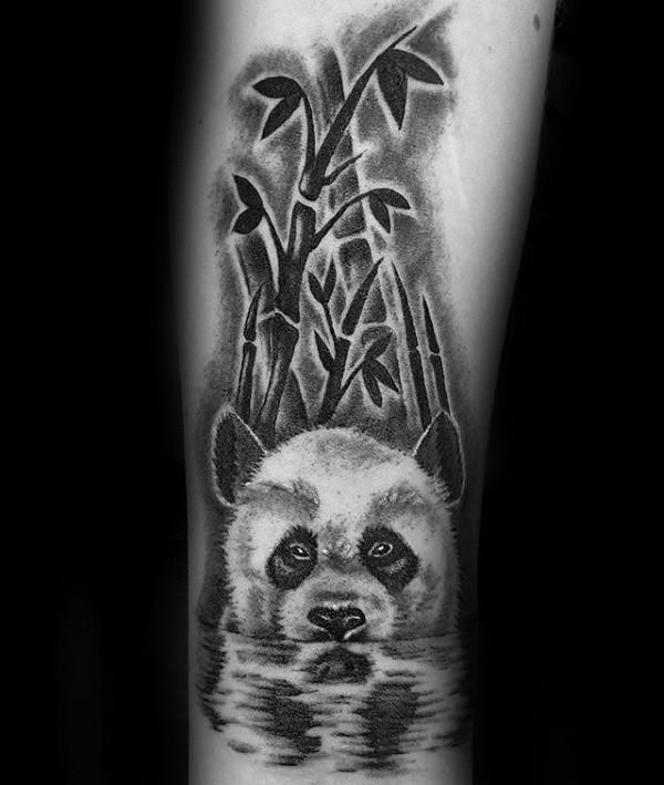 Nice natural looking arm tattoo of cute panda bear with bamboo