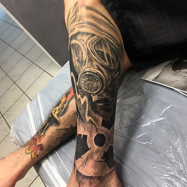 Nuclear war themed black ink leg tattoo of man in gas mask and radiation symbol