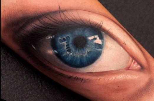 numero sette in occhio blu tatuaggio su braccio