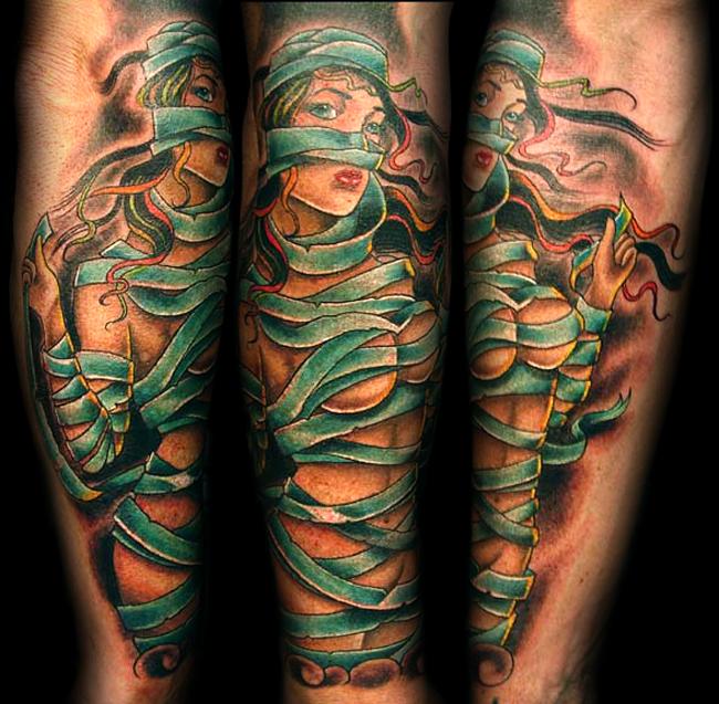 Old cartoon like colored forearm tattoo of seductive mummy like woman