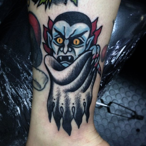 Old cartoon like colored vampire tattoo on ankle