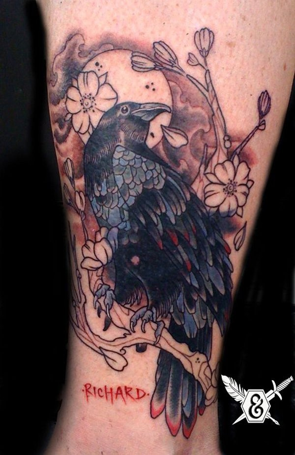 Old cartoon style colored bleeding crow with blooming tree tattoo on leg with lettering