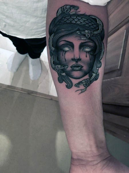 Old cartoon style painted and colored crying Medusa head tattoo on arm