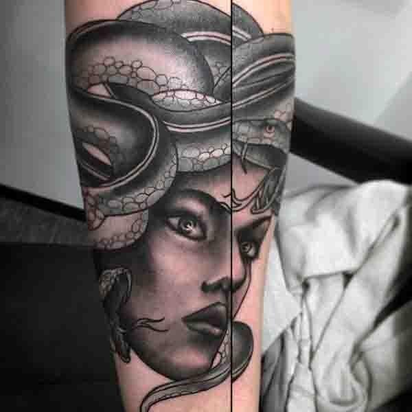 Old cartoon style painted black ink Medusa head tattoo on arm