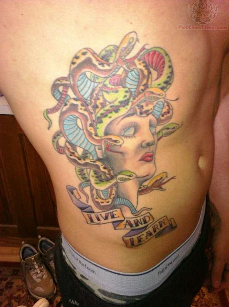 Old cartoon style painted colored Medusa head tattoo on side with lettering