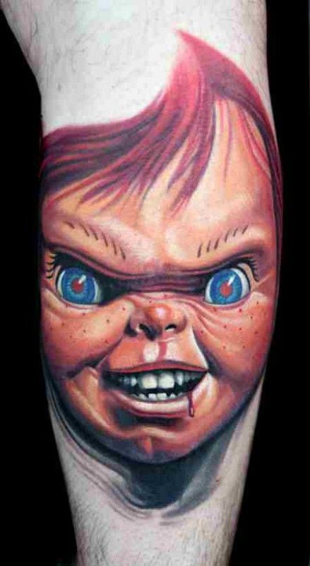 Old horror cartoon like colored evil bloody doll tattoo on arm
