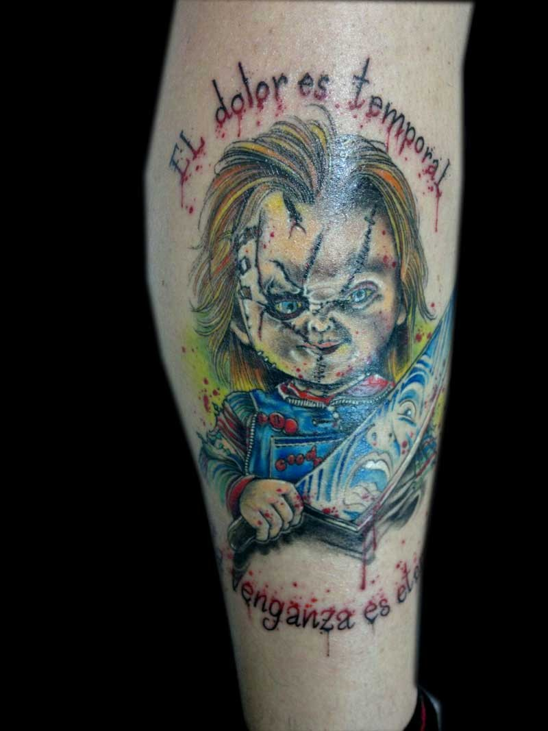 Old horror movie colored maniac doll tattoo on forearm stylized with lettering
