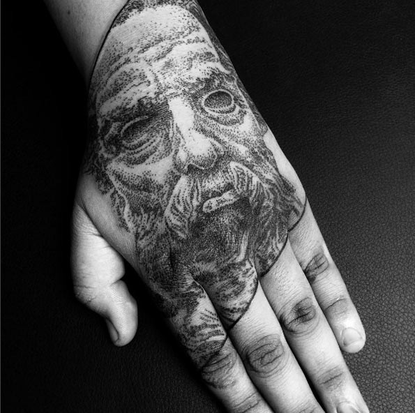 Old looking dot style hand tattoo of human portrait