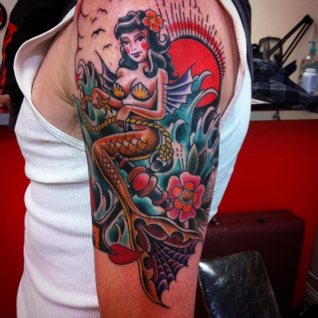 Old school beautiful looking colored mermaid with anchor tattoo on shoulder stylized with flowers and sun